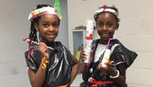 """Two girls pose wearing their """"trashion"""" creations."""