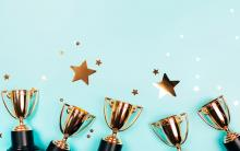 Photograph of gold trophies against a blue background with stars.