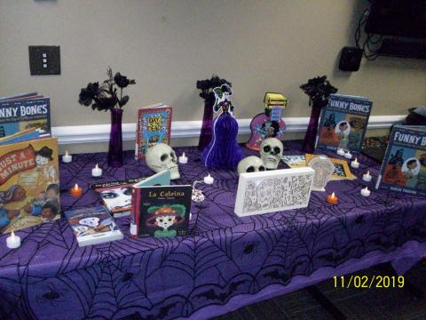 Traditional ofrenda or altar was made with books about Day of the Dead, tea lights, and wooden decorations