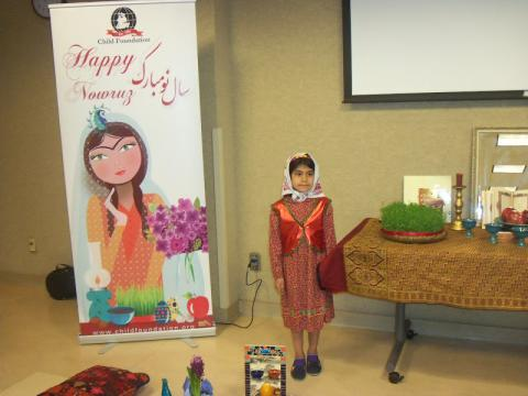 Child poses next to Nowruz banner