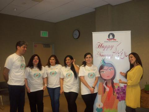 Nowruz Celebration volunteers pose next to banner
