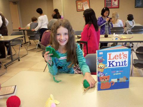 Student posing with her knitting project and a Let's Knit book