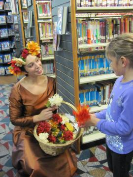 A staff member gives a girl flowers.