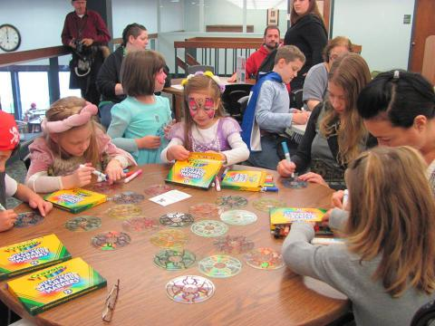 Children sit around a table and create stained glass using CD's.