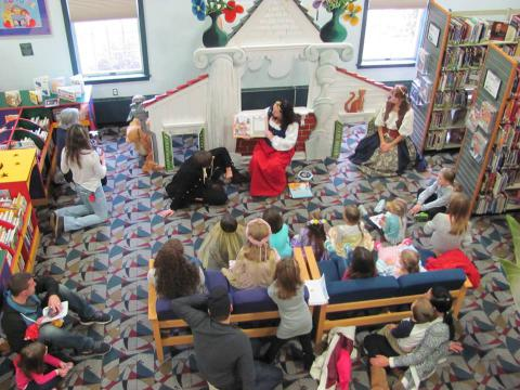 A staff member reads a book to a crowd of children.