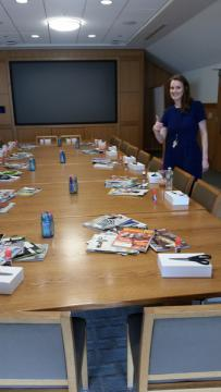 Magazines, boxes and supplies are spread across a long table.