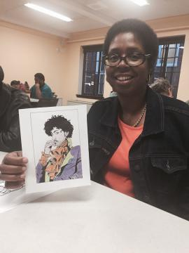 A woman smiles and shows off a photo of Prince that she colored.