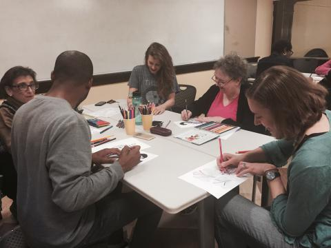 Five adults sit around a table while coloring photos with colored pencils.