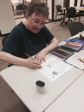 A woman is sitting down and coloring a photo.