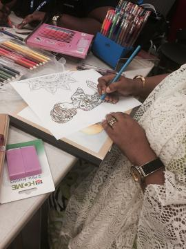 A participant is coloring a photo of a woman.