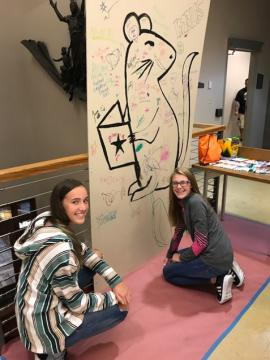 Teens drawing on the panel wall