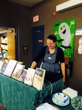 Woman standing behind a table with a book display