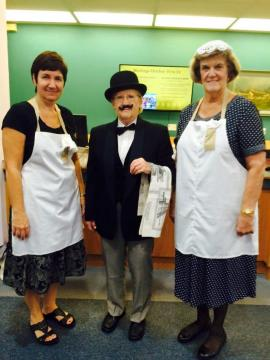 Three people, two in aprons, one in a suit
