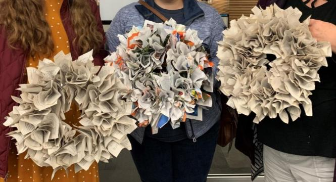 Patrons holding up completed book wreaths