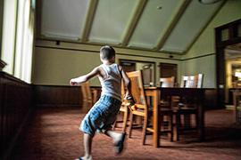 A boy runs around a table while playing laser tag in the library.