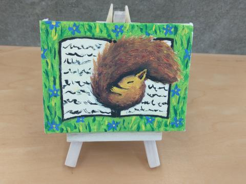 Photo of art canvas with painting of squirrel sleeping on book