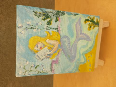 Photo of art canvas with painting of mermaid reading a book