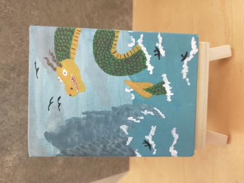Photo of art canvas with painting of a dragon in the ocean