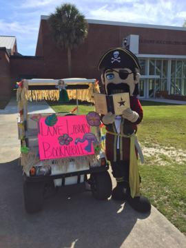 Pirate mascot reading a book next to golf cart
