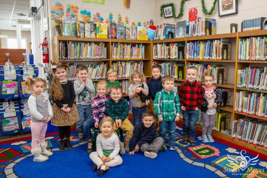 group of children sit in front of bookshelves