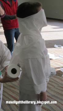 "A child being wrapped like a mummy from one of the ""Minute to Win it"" Games)"
