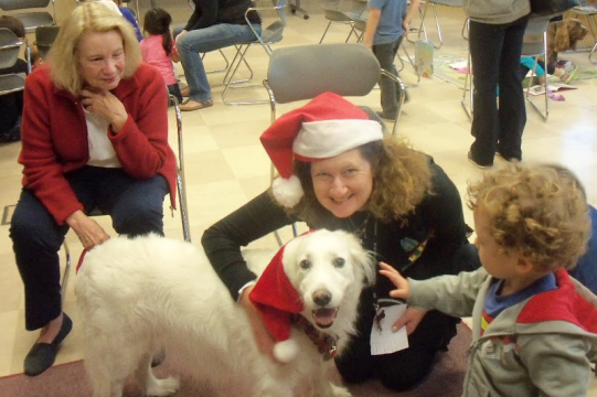 White dog wearing santa hat with owner and child