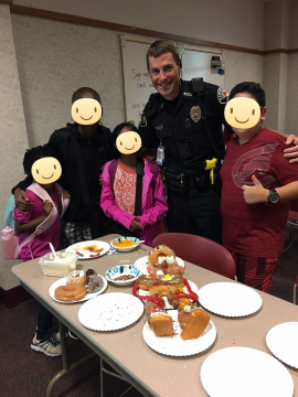 A police officer smiling with youth who made donut dioramas