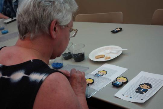 Attendee making a Perler bead Sherlock magnet