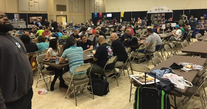 Large space filled with people playing games at tables