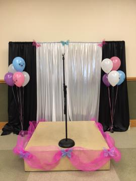 A stage for the tea party is decorated with balloons and butterflies.