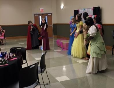 The women dressed as princesses are standing in front of the decorated stage.