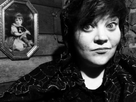 Photo of scary story teller in black and white with spooky background.