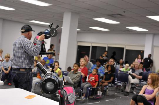 Man holds telescope and speaks to an audience