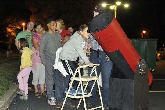 Group lines up to look through a telescope outside