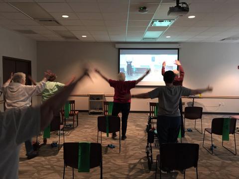 senior citizens doing a dumbbell exercise