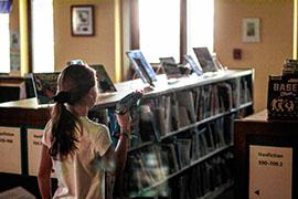 A girl stand between two bookshelves while playing laser tag in the library.