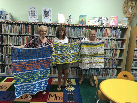 Three women holding up mats