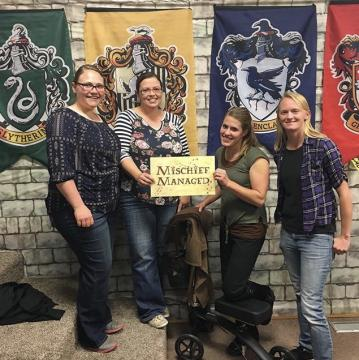 "Four people pose with ""Mischief Managed"" sign"