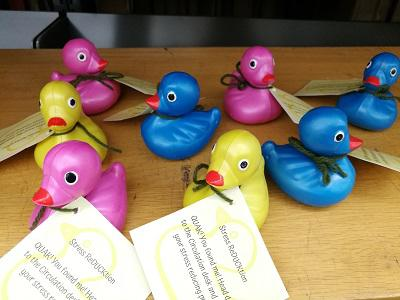 "Photo of a group of rubber ducks with notes attached saying ""Stress ReDUCKtion QUAK! You found me! Head down to the Circulation desk and claim your stress reducing prize!"""
