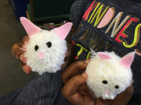 Child holding two pom-poms that look like bunnies
