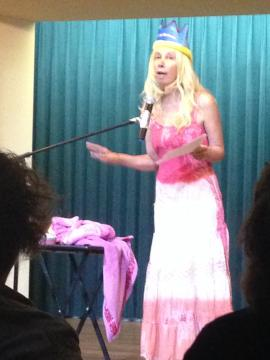 A woman stands in front of an audience and performs her memoir on stage.