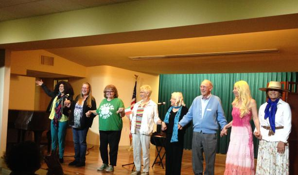 The participants finish performing their memoirs and stand on stage holding hands.