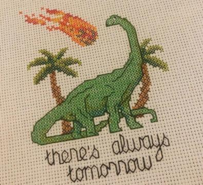 "Cross stitch of dinosaur with meteor. Text reads ""there's always tomorrow."""
