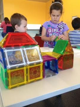 Two children build a house with Magna-Tiles