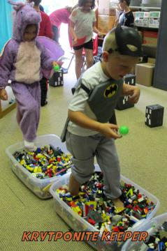 Children dressed as superheroes walk through tubs filled with Legos