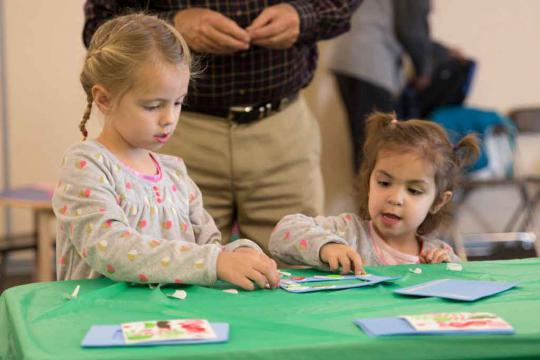 Girls making a craft at a Light Up the Holidays program