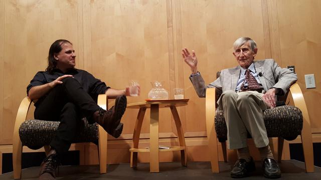 Nima Arkani-Hamed and Freeman Dyson sit next to each other while talking to a large crowd.