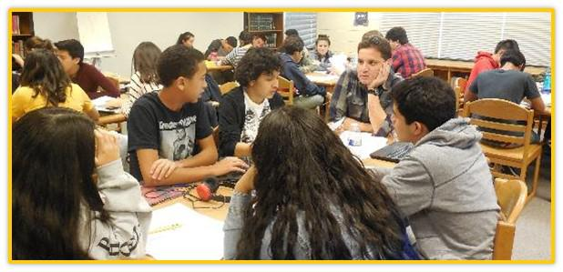 Students and John Parra talking at a table