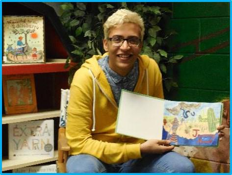Student poses with his illustrated storybook