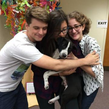 Three teens hug a puppy.